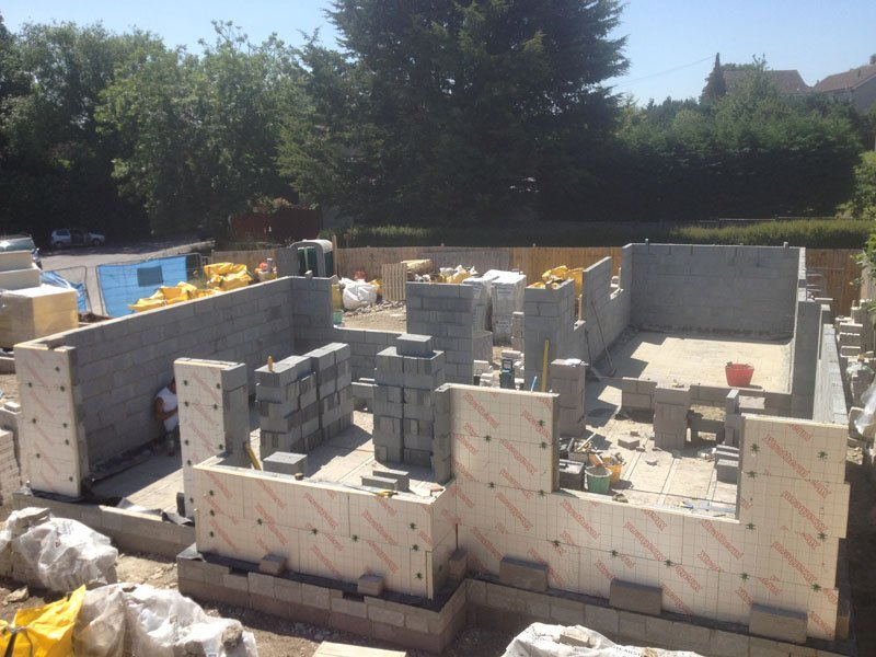 house foundation brickwork being laid on early building site